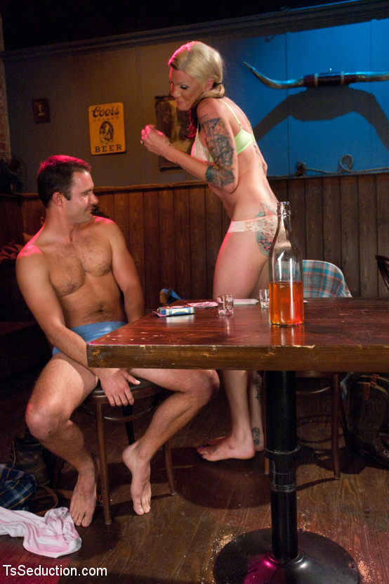 Tattooed hot blonde tranny and guy in bar sucking cock